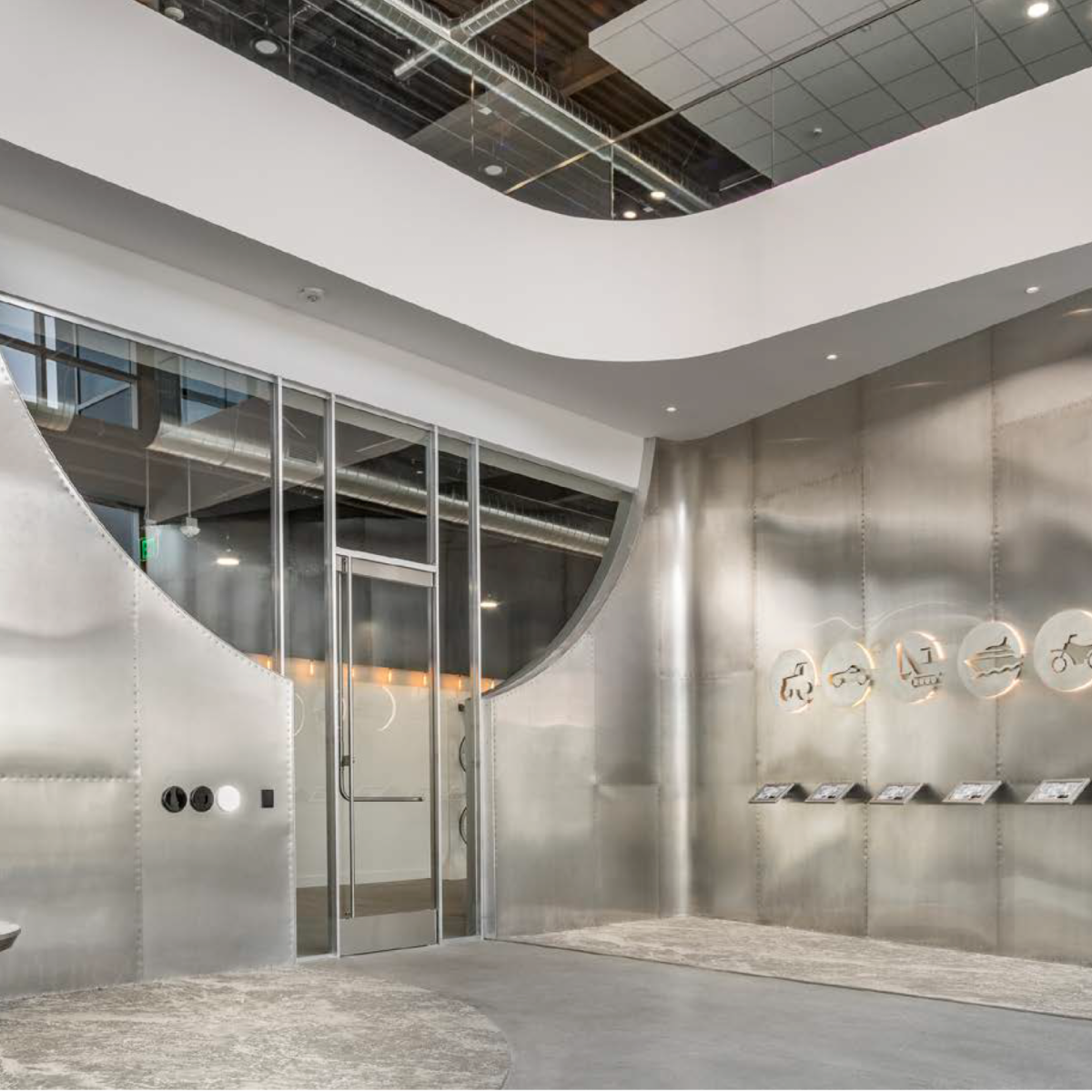 Lobby Clad in riveted Aluminum sheets and custom employee login stations below backlit Laser cut aluminum themes reflecting the firm's concentrations.